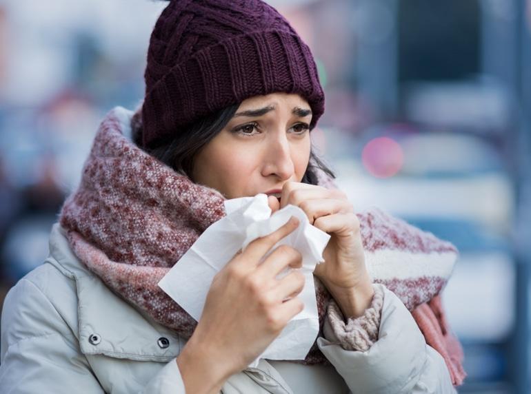 Млада жена, облечена със зимни дрехи, кашля в салфетка