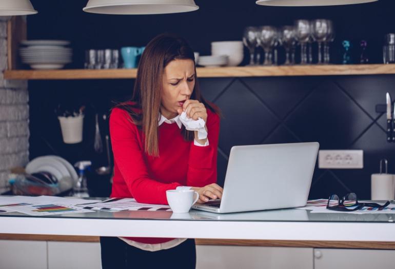 Какво причинява кашлицата? Жена, стояща в кухнята и работеща на нейния лаптоп, кашля в салфетката си