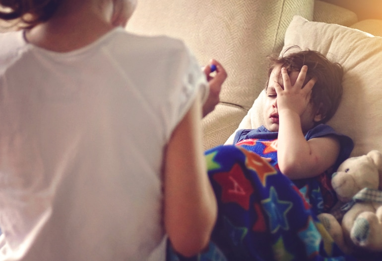 Болно дете с влажна кашлица лежии и се държи за главата